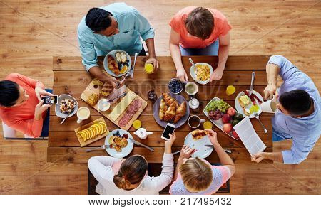 breakfast, technology and family concept - group of people with smartphones eating and photographing food at table