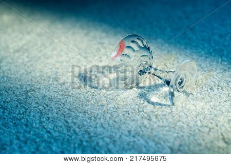 Champagne Glass With Lipstick Print Fallen On White Carpet.
