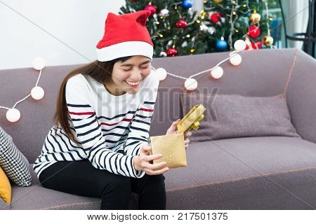 Asian woman close eye when open gold xmas gift box at holiday party on sofasurprise Christmas party present