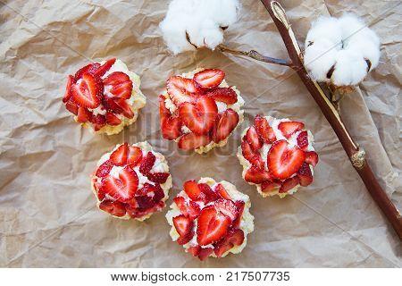 Very tasty muffins with fresh strawberries lie on kraft paper.