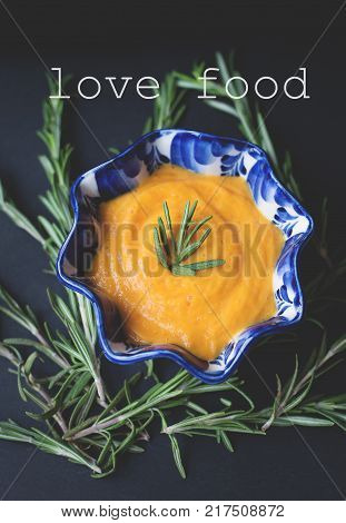 pumpkin soup on a black background with the sprigs of rosemary, inscription love food