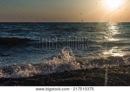 Droplets of seawater soared up after the wave struck against the shore at sunset.