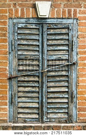 Blue wooden old window shutters on a vintage brick wall.