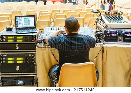 Sound technician and lights technicians control the music show in concert.Professional audio light mixer controller panel.Pro equipment for concerts.Stage lighting control.Hand adjusting audio mixer