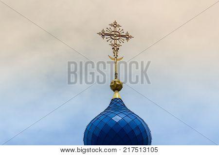 A yellow cross with a crescent on the blue dome of the temple against the sky with sunset or dawn.