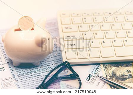Calculating tax for income tax return for saving tax target for save coin in the piggy bank. Tax and Saving Concept