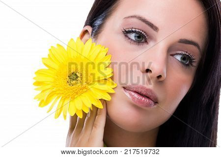 Beautiful girl with yellow flower looking wistfully