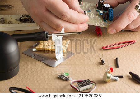 master repairs electronic equipment at his workplace