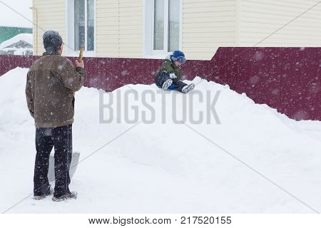 Grandfather playing with grandson on a snowy hill in winter
