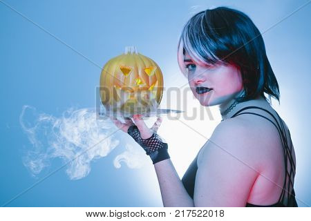 sexy waitress with a scary halloween pumpkin with cold iced smoke isolated in blue