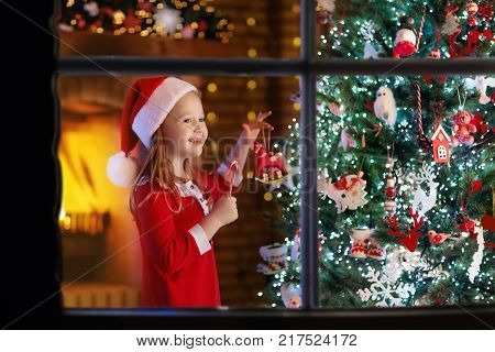 Child At Christmas Tree. Kid At Fireplace On Xmas