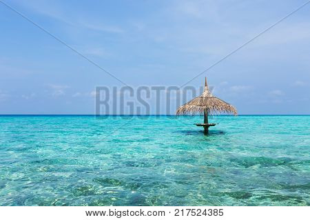 Single thatched sunshade umbrella at crystal turquoise sea water, nobody, travel destination card with copy space