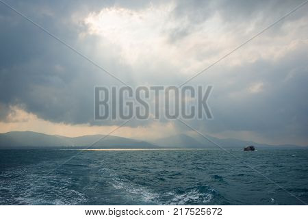 Sunbeams through hole in the clouds above ocean and a ship, silhouette of hilly Koh Samui, Thailand.