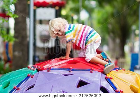 Kids on playground. Children play in summer park. Child on slide and swing on sunny day. Preschool or kindergarten yard. Daycare for young kid. Baby on play ground. Outdoor fun.