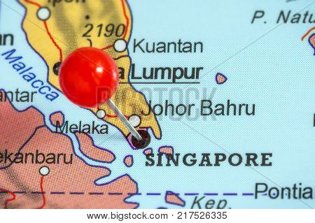Close-up of a red pushpin on a map of Singapore