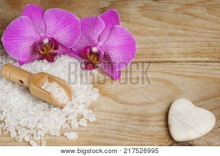 Bright orchid flowers next to white bath salt and a heart shaped stone on a wooden table.