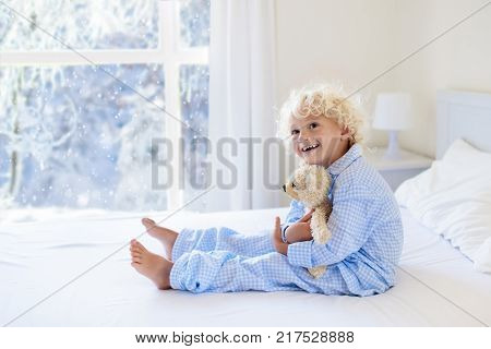 Kid In Bed. Winter Window. Child At Home By Snow.