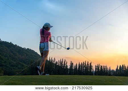 Asian woman golf player doing golf swing tee off on the green sunset evening time she presumably does exercise. Healthy and Lifestyle Concept.