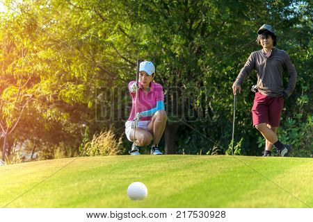 Woman golf player squatting to analyze the green for putting the golf ball into the hole with man player. Lifestyle Concept.