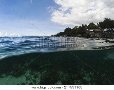 Double landscape with sea water and cloudy blue sky. Tropical seaside photo. Above and below waterline. Seawater surface. Beach view from sea. Tropical sea view banner. Above and below sea waterline
