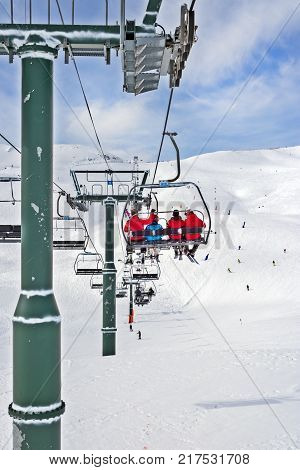 PYRENEES ANDORRA - FEBRUARY 11 2017: PIillar of the line of the elevator and chair of the elevator with skiers in ski resort. A view of people in bright clothes on the elevator behind. The Pyrenees Andorra routes with riding below