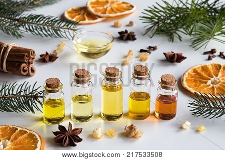 Christmas selection of essential oils and spices on white background: bottles of essential oil spruce fir frankincense resin star anise cinnamon clove dried orange.