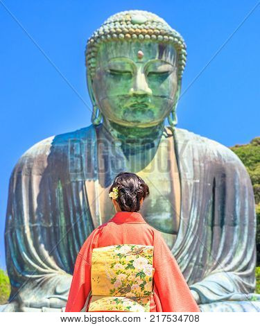 Unidentifiable woman wearing Japanese kimono looking Great Buddha or Daibutsu. The monumental Buddha Vairocana in Kotoku-in Temple is one of main attractions in Kamakura, Japan.Hanami in spring season