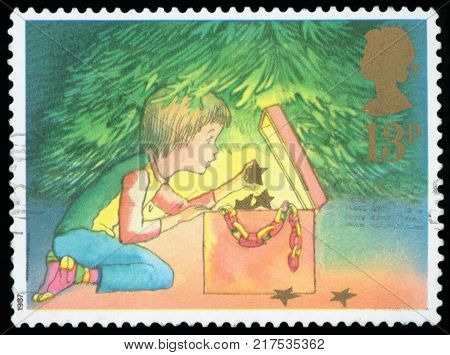 UNITED KINGDOM - CIRCA 1987: A stamp printed in the United Kingdom shows Childhood opening a Christmas present, circa 1987