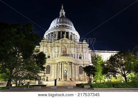 The illuminated front facade of St Pauls Cathedral at night. Iconic London tourist attraction designed by Sir Christopher Wren in the late 17th century.