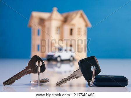 Car key and house keys with new automobile and home on background with copy space. Concept of buying, selling and renting a car and house