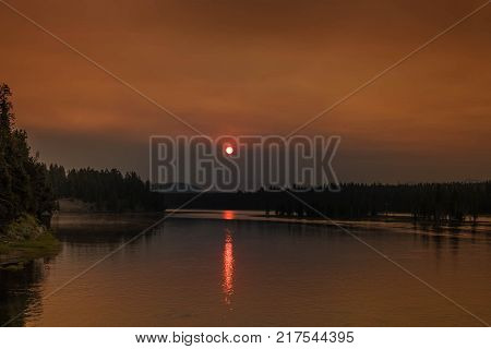 Red sunrise reflecting in the clouds over the lake the trees are silhouetted and reflecting in the lake horizontal