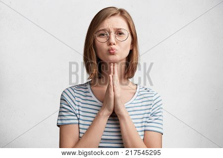 Pleading female student rounds lips and has sorrorful expression asks professor for permission to repass exam wears round spectacles and striped t shirt isolated over white concrete background