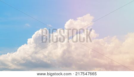 White cloud on blue sky. Cloudscape photo background. Romantic skyscape with cloud and pink sun flare. Stormy cloud on sunny sky. Climate or weather change. Moisture concept. Fluffy cloud closeup