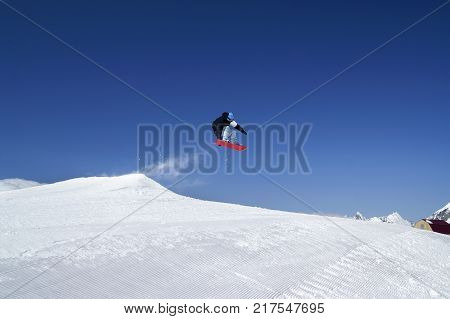 Snowboarder jump in terrain park at ski resort on sunny winter day. Caucasus Mountains region Dombay.