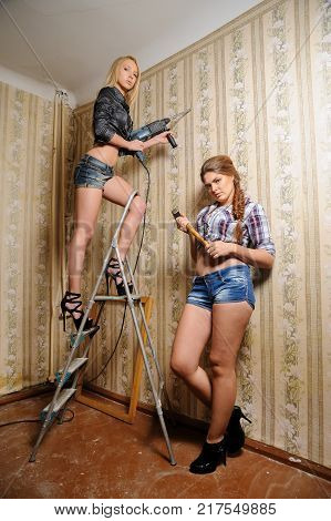 Two attractive women with puncher and hammer do reconstruction in room