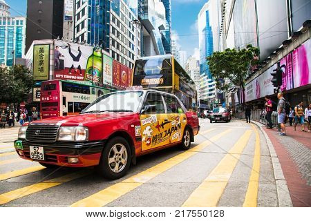HONG KONG -  APR 3, 2016: Urban red taxi in Hong Kong urban landscape on Apr 3, 2016. Hong Kong is an autonomous territory on the Pearl River Delta of East Asia.
