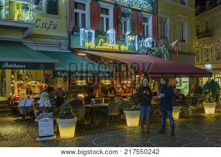 Street with restaurants and terraces in historic city center with Christmas decorations on December 9 2017 in Baden-Baden Baden-Wurttemberg Germany.