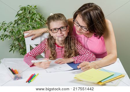 Mom helps her daughter elementary school pupil in her notebook, at home at the table.  Back to school concept.
