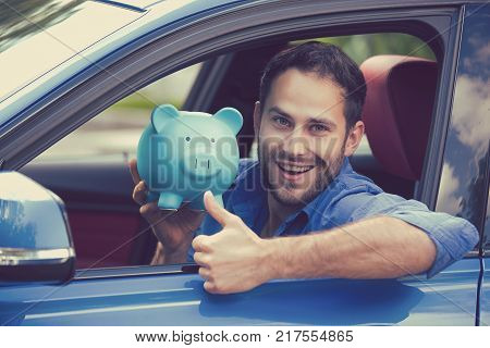 Happy man sitting inside his new car holding piggy bank showing thumbs up