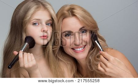 First make-up. Portrait of cheerful mother and her lovely pensive little daughter are looking at camera while posing with naked shoulders. They are holding brush while applying powder. Isolated