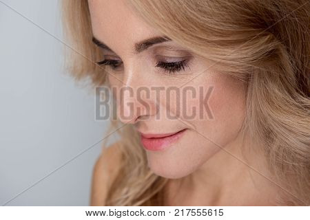 Close-up of face of gorgeous sensual middle-aged woman is posing with naked shoulders and looking down wistfully. Isolated background and copy space