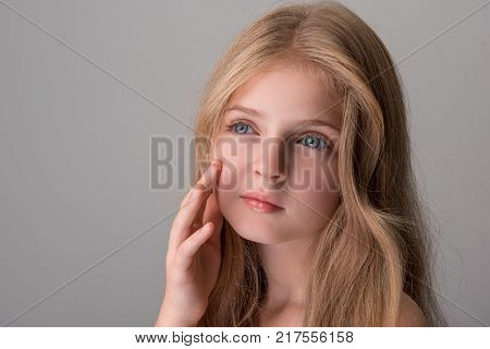 My perfect skin. Close-up portrait of wistful lovely little girl is standing and looking aside dreamily while touching her face tenderly. Isolated background. Copy space in the right side