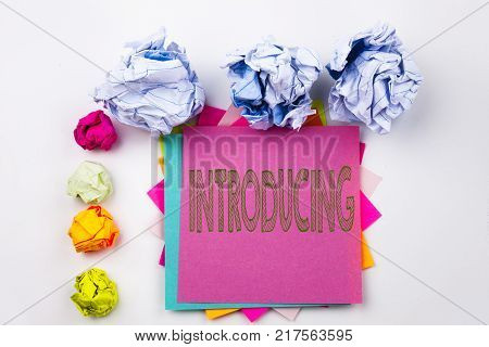 Writing text showing Introducing written on sticky note in office with screw paper balls. Business concept for Introduction Start Intro Beginning on white isolated background.