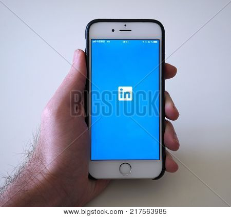 Wuhan China, 9 December 2017: Man holding smartphone with LinkedIn employment oriented social networking service app loading screen with LinkedIn logo
