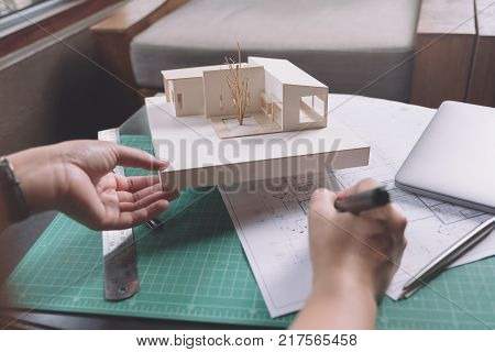 Closeup image of architects drawing shop drawing paper with architecture model on table