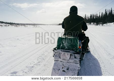 in the far cold north, a man in warm clothes rides a snowmobile through a snow-covered field