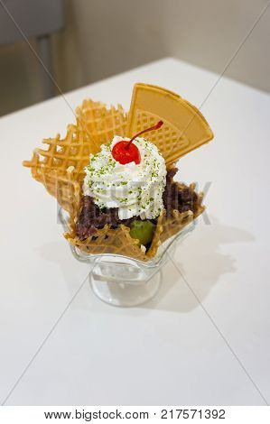 sundae ice cream with whip cream wafer sweet cherry kidney bean in cup on white table.