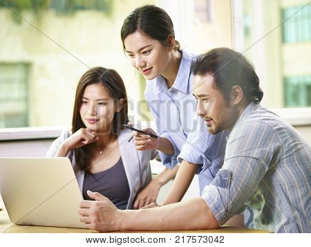 team of young asian business people in casual wear working together in office using laptop computer.