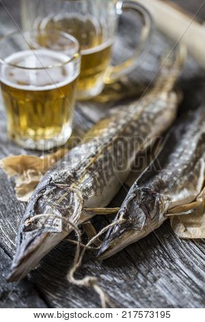 fish pike, dried with a glass of beer on wooden boards