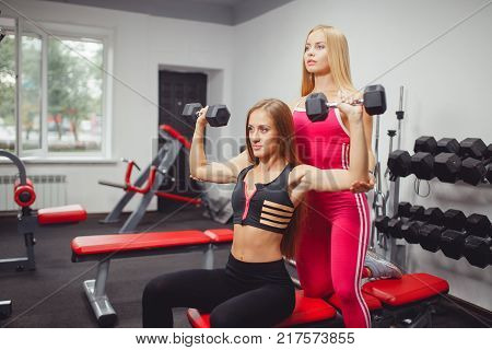 Individual training with a body fitness trainer, the concept of doing sports in the gym with dumbbells